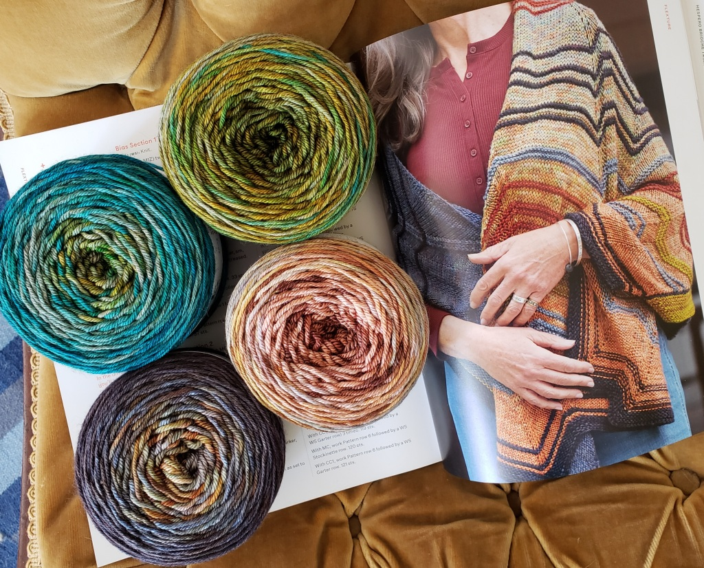 Four cakes of yarn rest on the book Custom Shawls, open to a a page showing a model wearing Flexture.  The yarn is two gradients: teal to acid greens and slate grey to reddish tan.