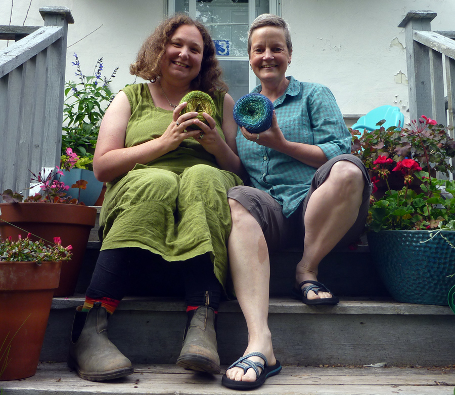 Two white women sit on wooden steps. Elizabeth, a fat woman in a green dress, holds a green cake of yarn; Marit, with very short hair and a teal plaid shirt, holds a teal to blue cake of yarn.