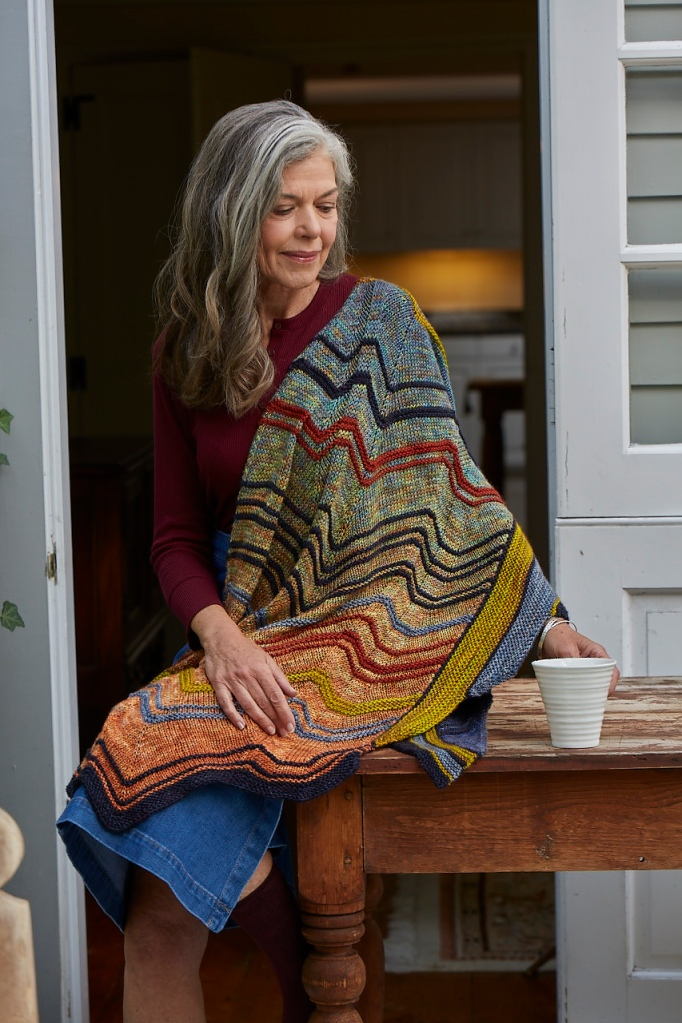 A woman modeling Flexture, a shawl with colorful stripes on an orange-to-blue gradient. The model has long grey hair and is perched on the edge of a table holding a mug.