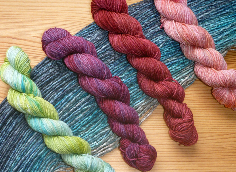 Four mini-skeins lying on the dark blue to grey gradient. The minis are pale aqua and green, dark magenta-purple, deep red, and soft heathery pink.