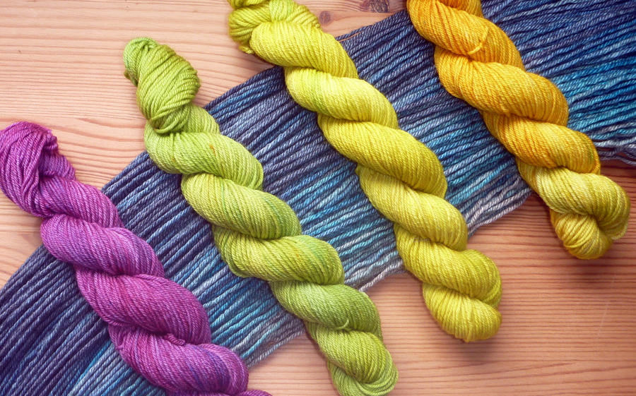 Four mini-skeins lying on the dark blue to grey gradient. The minis are reddish purple, spring green, acid green, and golden yellow.