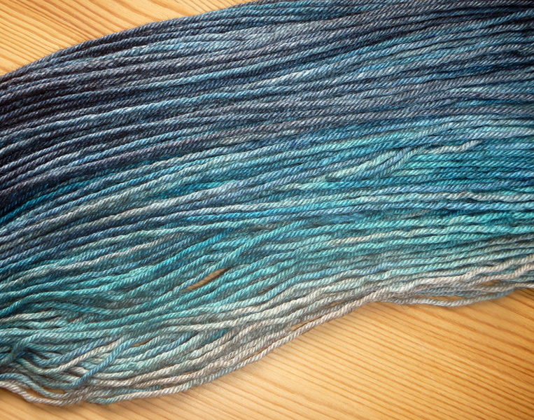 A close-up of gradient yarn, from deep navy through soft turquoise and aqua to warm grey.